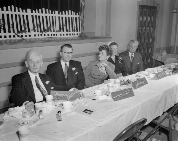 Left to right at the head table of the Madison Advertising Club Bosses' dinner are: Ralph O'Connor, WISC manager and club president; Burton Bigelow, sales expert and lecturer; J.A McIlnay; Mrs. Bigelow; Mrs. (Pearl) McIlnay; Dean F.H. Elwell, University of Wisconsin school of commerce; and John Reese, program chairman.