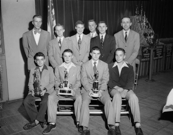 Group portrait of members of the Blessed Sacrament Parochial school athletic teams, their coaches and sponsors who were honored at the school's annual banquet. Front row left to right: Jack Valentine, David Hackworthy, Mike Donagan, and Dan Lamphear. Back row: Lou Genter, Knights of Columbus; Buck Asper; Pat Heffernan; Ed Miller, football and baseball coach; Earl (Shorty) Ross, basketball coach; and Don Purcell, Catholic War Vets.