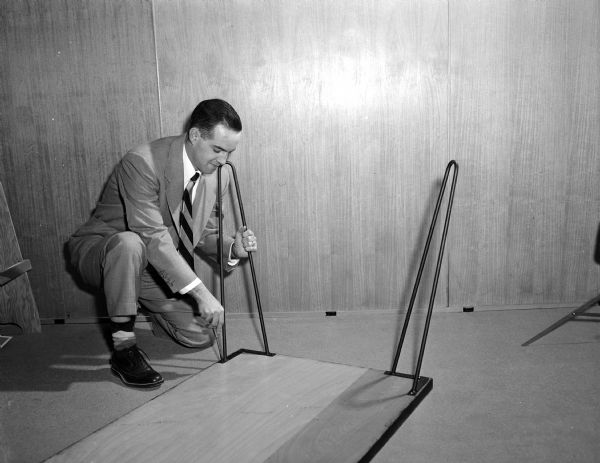 A man, possibly Mr. Collins, attaches metal legs to a wooden table top.