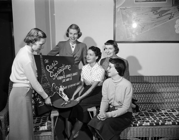 Committee members plan the dinner-dance for the Maple Bluff Country Club. They are shown with one of the posters announcing the event. From left to right are Lorraine Wilkie, Bette Sonneland, Nancy Taborsky, Betty Vaughn, and Elizabeth Hubbard.