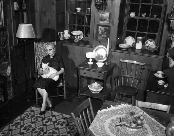 Lenore Middleton (Mrs. Forest Middleton) poses with her cat in the antique-filled living room of her home at 3241 Highbury Road (address in 1955). The home was built in 1853 by Joseph Statz and is to be featured on the second annual house tour of the League of Women Voters in cooperation with the Madison Chapter of the Wisconsin Division of Architects.