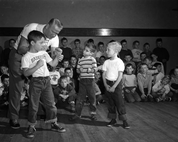 "Vern Woodward, University of Wisconsin assistant boxing coach, helps young students during a ""Little Boxers"" class at the Eagles Club, 23 West Doty Street. Woodward helps Ronnie Eservig take the proper boxing stance while Ricky Raznikov, center, and Tommy Wagner, right, watch."