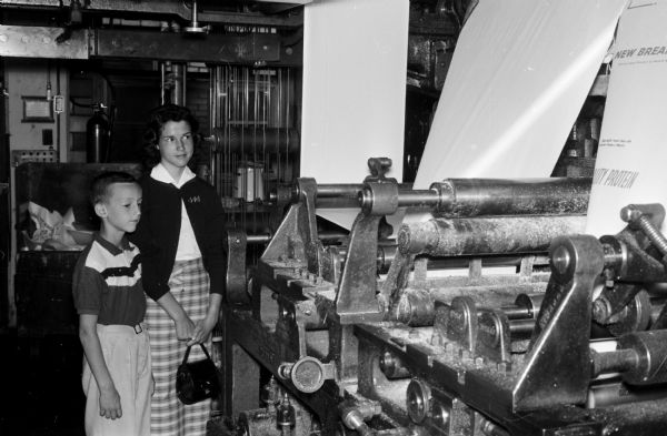 Pat, 8, and Vicki Rohan, 14, examine some of the equipment in the press room of Madison Newspapers, Inc. The photograph was taken for part of an article suggesting Madison places and activities for summertime visiting.