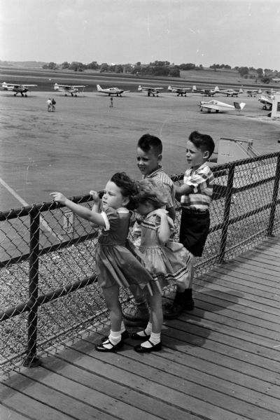 Four children stand on the observation deck watching planes at the Madison Municipal airport. The children include, from left to right: Carol, 3, Christine, 4, Michael, 8, and Stephen, 9. Their parents are Mr. and Mrs. Richard Usher of Montgomery, Alabama. The photograph was taken as part of an article suggesting Madison places and activities for summertime visiting.