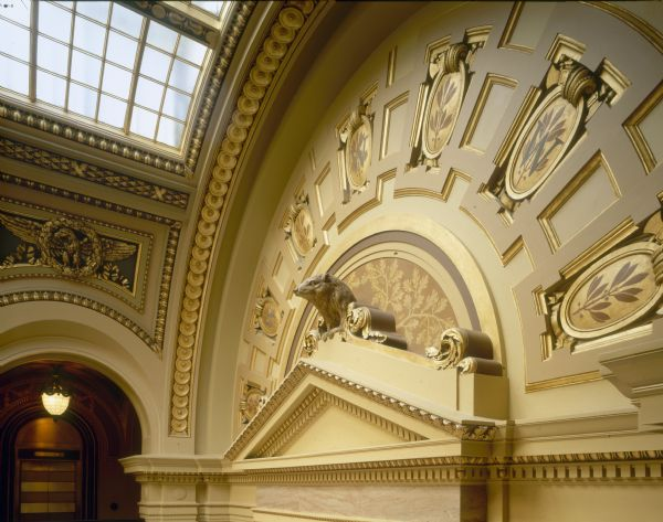 Badger sculpture above door of second floor chambers, in the Wisconsin State Capitol, with skylight in background.