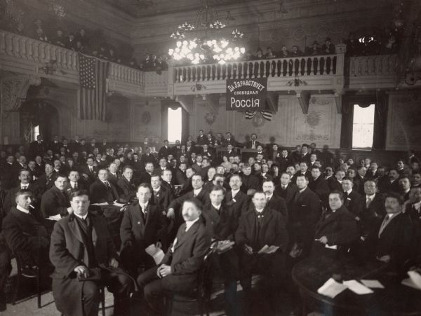 "A convention of Russian immigrants at Beethoven Hall in New York City.  The newspaper caption for this photograph describes the Bolshevik communist faction as having used ""steam roller"" tactics which caused a storm of protests from the representatives of other organizations that were present."