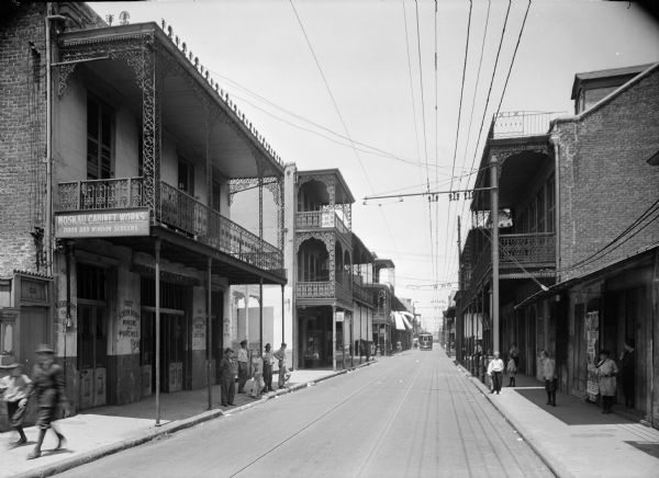 "New Orleans street scene. Pedestrians can be seen on the sidewalks, and a streetcar can be seen in the distance. ""Moskau Cabinet Works, door and window screens"" can be read on building on the left side of the street."