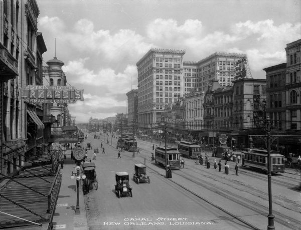 "Canal Street scene, New Orleans, Louisiana. Automobiles, streetcars and pedestrians can be seen in the busy street. Store sign reads: ""Stein-Block LAZARD'S Smart Clothes."" Text on photograph reads: ""Canal Street, New Orleans, Louisiana."""