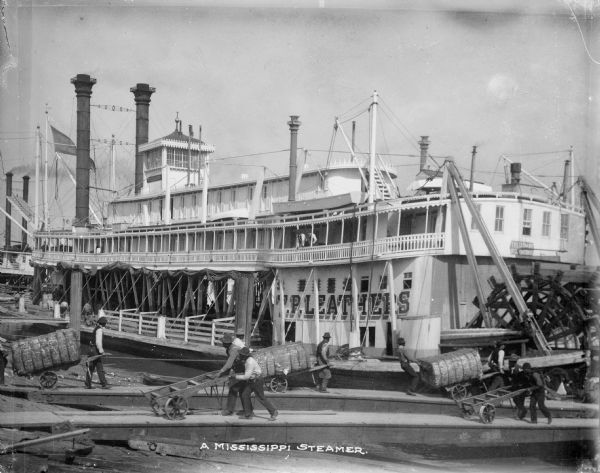 "View of the T.P. Leathers Steamer at dock. Men can be seen loading cargo onto the ship. Text on photograph reads: ""A Mississippi Steamer."""