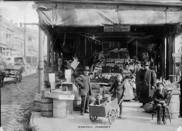 "View of shoppers in the French market in New Orleans, Louisiana. One boy is shown pushing two small children in a cart. Fruits and vegetables can be seen in the market stall in the background. Text on photograph reads: ""French Market"""