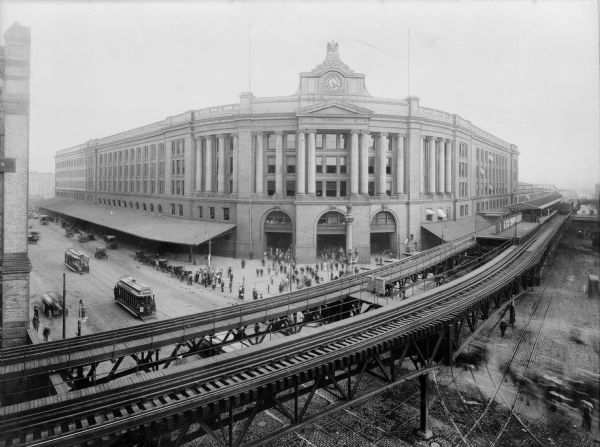 View of the South Station terminal with elevated track in the foreground, Boston, Massachusetts. Streetcars and pedestrians can be seen on the street below. The South Station was created in the late 1890s when it was no longer efficient for each of the five railway companies that serviced Boston to have their own depot.