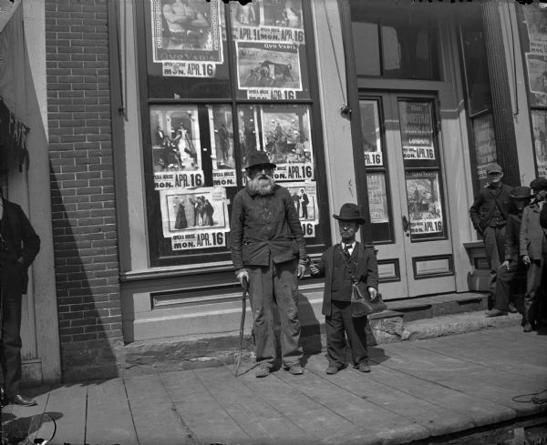 "Two men posing standing in front of the Fair Store on Main Street. The man on the right is a dwarf and he is holding a cigar. Posters in the windows advertise ""Quo Vadis at the Opera House on Monday, April 16"" by the Courtenay Morgan Company."