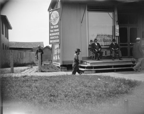 "Men at the Mose Bone Sample Room. Two men are sitting on chairs on the porch in front. A male dwarf is walking on the board sidewalk in front of the saloon, which is north of the railroad depot. A sign on the building advertises ""Drink Schlitz, the Beer that Made Milwaukee Famous, For Sale at Mose Bones."" There is a sign painted on the side of the building advertising ""Cigars, Lunch Room, and Lodging."""