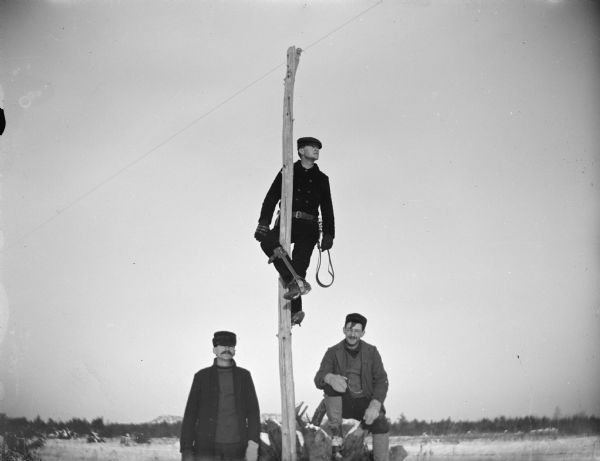 Man posing on a telephone pole with climbing equipment, with two men standing below.
