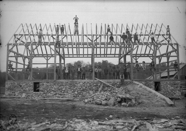 "Barn raising. The foundation is constructed from local fieldstone or ""pudding stone,"" found in the nearby fields. A large group of men are is posing holding an infant, and a young boy is standing and holding the hand of another man."