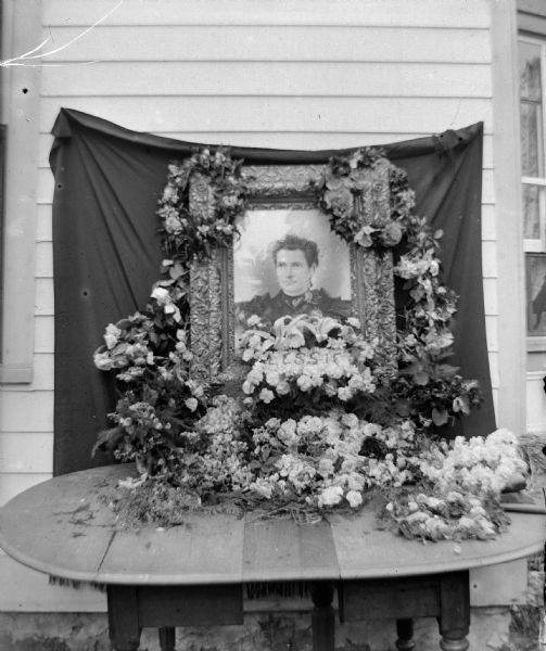 "Bouquets and wreaths decorating a portrait of ""Lessie,"" on a table on the side of a house."
