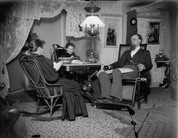 Amos Elliot, pioneer stage coach driver, enjoying a quiet evening at home with his second wife, and her daughter (center), Stella Hart.