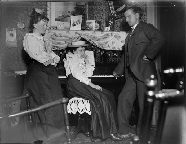 Two women and a man posing by a piano.