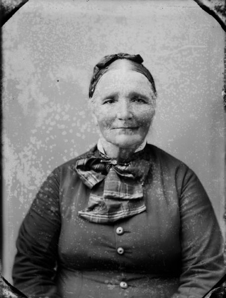 Studio portrait of a seated elderly woman wearing a head scarf and a large plaid necktie.