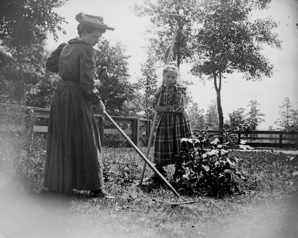 Woman in hat and young girl raking the lawn.