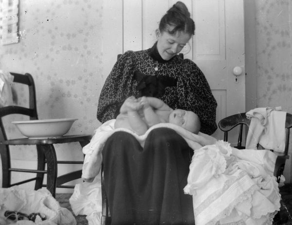 A woman bathing an infant on her lap, probably Julia (Murray) Ormsby.