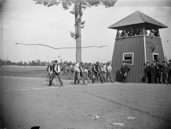 Four cyclists await the start of a race at the Jackson County Fairgrounds. There is a viewing pavilion on the right.