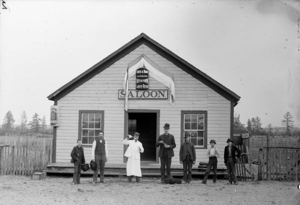 "Bartender and six patrons posing in front of a saloon. The saloon sign reads: ""Celebrated Watertown Lager Beer."""