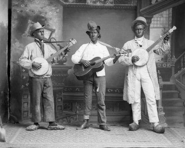 Three musicians, two males with banjos and possibly a woman with a guitar, pose in blackface and costumes for a studio portrait in front of a painted backdrop.