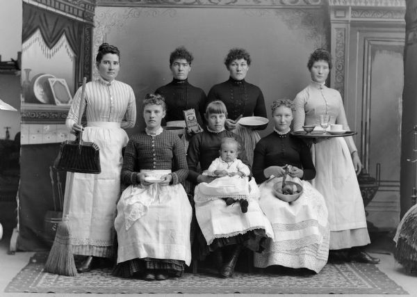 The household staff (probably Swedish) for one family home, including laundresses, cooks, parlor maids, and scullery girls with their various work utensils. One woman is holding an infant. They are posing in front of a painted backdrop.