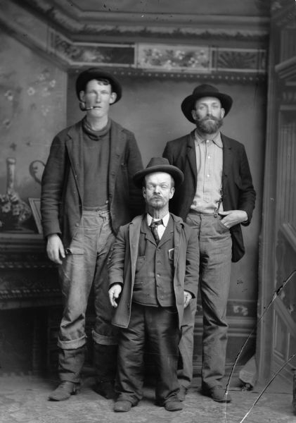 Studio portrait of three men standing, one of whom is a little person, standing in front of a painted backdrop. All of the men are wearing hats, and the man on the left has a pipe in his mouth.