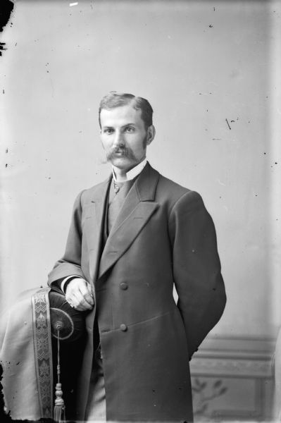Studio portrait of a standing man with his arm on a stuffed chair, possibly a self-portrait of Van Schaick. He has a moustache, and is wearing a long jacket over a vest and high-collared shirt.
