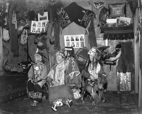 A European American woman and two boys posing sitting and a European American girl posing standing, all dressed in Ho-Chunk regalia. They are in a room decorated with Ho-Chunk artifacts and photographs, and the artifacts are probably from the collection of Tom Roddy.