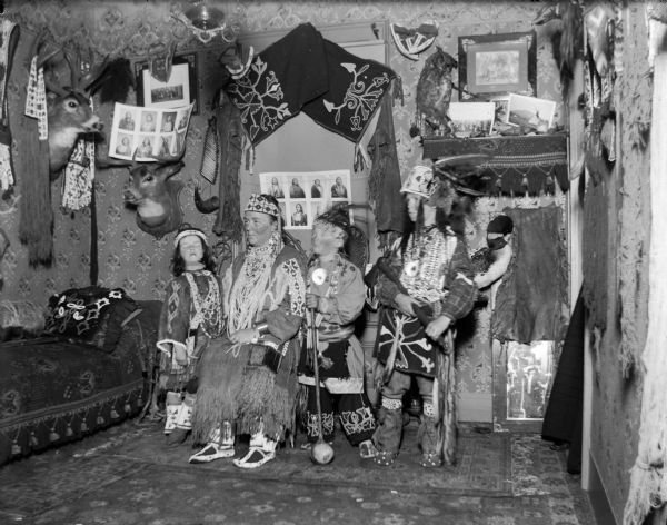 European American woman posing sitting, and a European American girl and two boys posing standing, all dressed in Ho-Chunk regalia. They are in a room decorated with Ho-Chunk artifacts and photographs. The artifacts are probably from the collection of Tom Roddy.