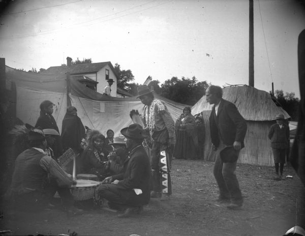 Ho-Chunk men and women sitting and standing around a large medicine drum in an area portioned off by canvas barriers in front of a lodge. Identified as the Homecoming Powwow in 1908 at the intersection of Main and Second Streets. A house on a hill can be seen in the background