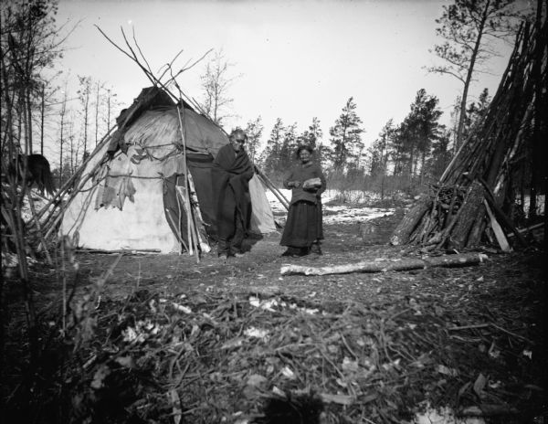 A Ho-Chunk man and woman posing standing in front of a Ho-Chunk winter lodge. The man is reportedly blind. In the background there is a horse and snow on the ground.