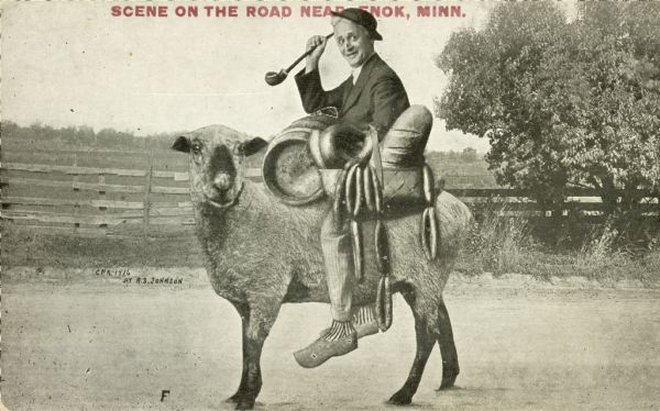 "An older man is riding a sheep on a dirt road. He has a small barrel, some sausage links, and a loaf of bread. The object in his right hand appears to be a crop. A fence protects a pasture in the background.  The image was pieced together from a number of sources; a close look betrays that the man's legs are fake. Red text in the upper portion bears the inscription ""Scene on the Road near Enok, Minn."""