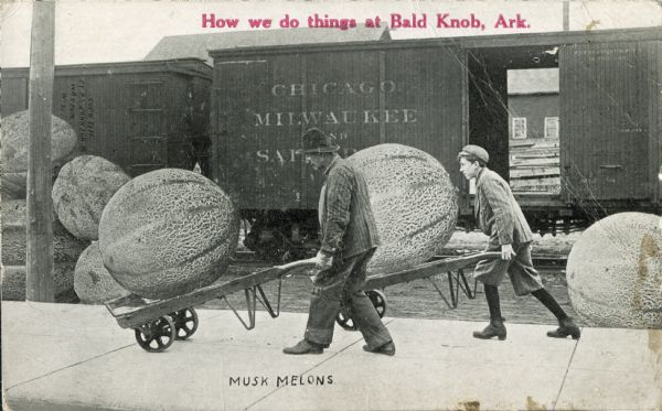 "A man and a boy use dollies to haul giant musk melons near a train. In red text on the upper center portion is the inscription, ""How we do things at Bald Knob, Ark,"" suggesting that this postcard, though photographed in Waupun, was distributed as an image of Bald Knob, Arkansas. The train in the background reads, ""Chicago, Milwaukee and Saint Paul""."