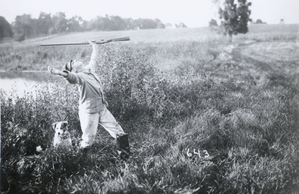 "Photographic mock-up for an Alfred Stanley Johnson photomontage postcard entitled ""Kickers."" A boy wearing waders and holding a rifle stands with his arms outstretched and his face toward the sky. A dog is by his side; the two are standing by the shore of a pond."