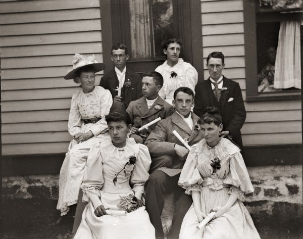 Eight men and women of a graduating class sit outdoors holding their diplomas. They are seated on the steps of the photographer's home at 131 East Montello Street.