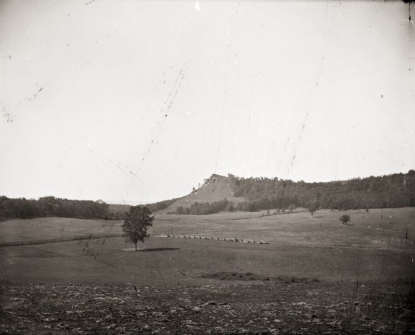 Distant view of Black Hawk Lookout near the Wisconsin River. Open field with single tree and fence in foreground.