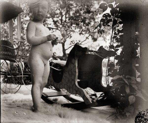 Everetta Bass, the photographer's daughter, standing nude next to rocking horse. She, along with the rocking horse and a baby carriage, are on an unidentified front porch.