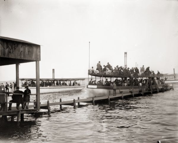 "Two steamboats docked at Lake Monona. Boat in foreground is identified as ""Lake Side"". A third boat is in the background."