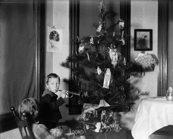 Cary and Everetta Bass with their Christmas tree. Cary holds a toy horn; Everetta holds a doll.