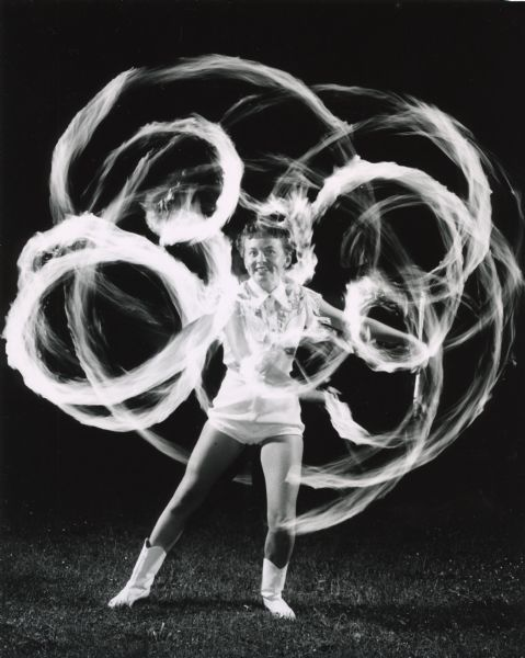 Outdoor photograph of a young woman twirling batons with flaming ends.