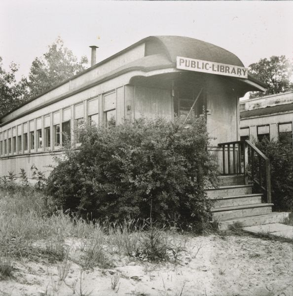 Public Library housed in a stationary railroad car in Adams, WI. The train car was a gift from F. W. Sargent of the North Western Road at the request of Mrs. J. F. Duncan and Mrs. Pearly Bennett of the Adams Library Association.  Mrs. Hazel Fease worked to make the train car into a subscription library.