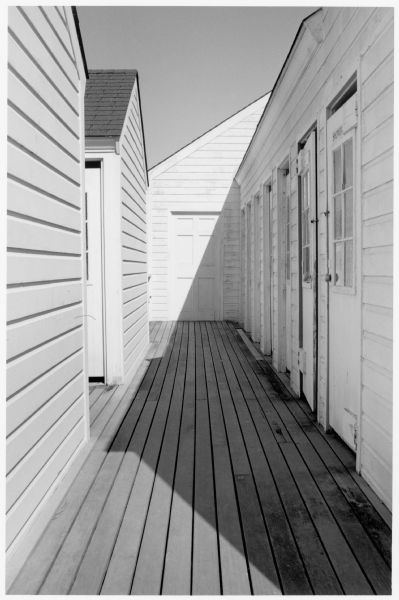 Wooden boardwalk surrounded by white dwelling.