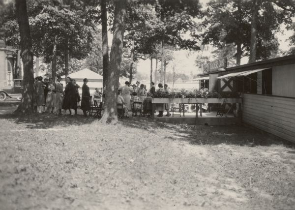 Summer camp for Wisconsin farm women on the grounds of the Wisconsin State Fair with Wisconsin home economics leader Nellie Kedzie Jones. Mrs. Jones is probably the woman near the tree with her back to the camera.