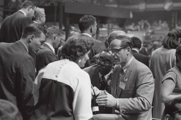 Midge Miller of Madison talks with an unidentified supporter of Eugene McCarthy at the Democratic Convention.  Listening intently to their conversation is Hilton Hanna, also of Madison and a leader of the Alamgamated Meatcutters and Butchers of North America.