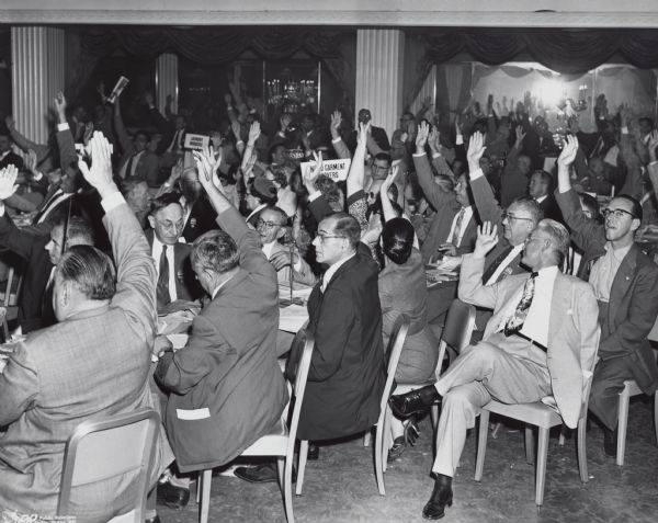 Raising their right hands, an unidentified group of union members votes at the American Federation of Labor (AFL) convention.