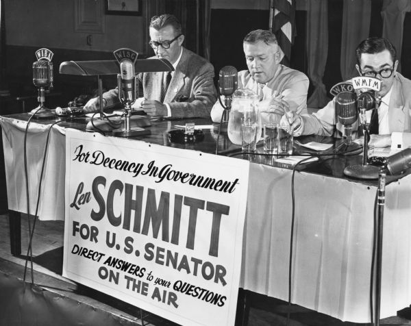 "Len Schmitt, former Progressive Party legislator from Merrill, led the Republican opposition to Senator Joseph R. McCarthy's bid for re-election. Schmitt attempted to call attention to his ""Decency in Government"" campaign with a 25-hour radio talkathon. He is seated here with Mike Griffin, a radio announcer and his campaign manager; a local radio announcer is to his left. Schmitt anticipated there would be no Senate primary race on the Democratic ticket which would have allowed Democrats to cross over and vote for him. Instead there was a tight race between Henry Reuss and Thomas Fairchild. Senator McCarthy handily defeated Schmitt in the primary."
